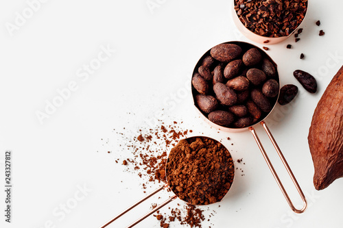 Fotografía  Rose gold measuring cups of cocoa beans, cacao nips, cocoa powder and cocoa pods