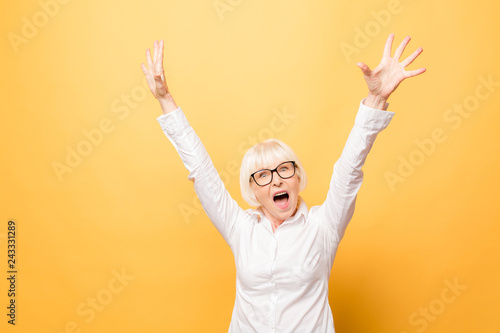 Fotografía  I'm winner! Portrait of a cheerful senior woman gesturing victory isolated over yellow background