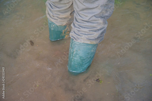 Men's foots in rubber boots in the muddy water