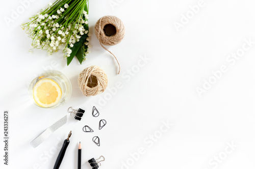 Poster de jardin Muguet de mai Composition with rolls of twine rope, bouquet of lilies of the valley, glass of water with lemon, stationery