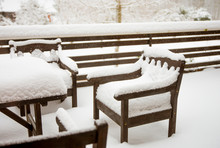 Fresh Clean Snow Covering Brown Wooden Mahogany Color Stained Garden Chairs And Table On Home Balcony. Garden Furniture Maintenance After Cold Winter Concept.