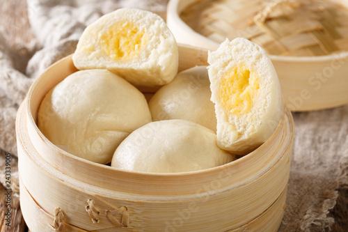Chinese traditional steam custard buns closeup  in bamboo steamer. horizontal