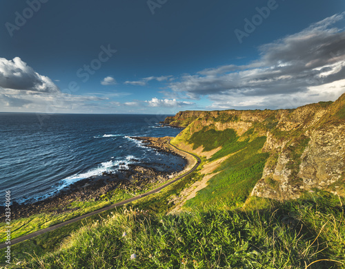 The road passing through the Northern Ireland shoreline. Breathtaking Irish landscape. Grass covered fields next to the ocean water surface. Cloudy sky background. Picturesque panoramic overview.