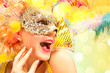 Leinwanddruck Bild - Beautiful surprised woman in carnival mask. Beauty model woman wearing masquerade mask at party over holiday background with magic glow. Christmas and New Year celebration. Glamour lady with perfect