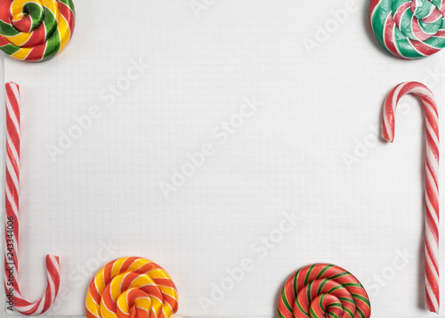 colorful sweet candys on blank notepad. striped Candy Canes and spiral lollipops on paper exercise book in a cell, mockup