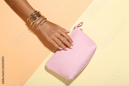 Fotografia Female hand with bracelets and handbag on colorful background
