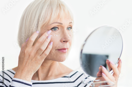 Fotografía  Beautiful elderly woman holding mirror and applying face cream