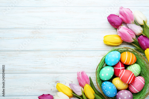 Fotografiet  Colorful easter eggs in basket with tulips on wooden table