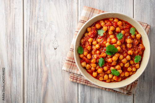 Spicy Chickpea curry Chana Masala in bowl on wooden table. Traditional Indian dish. Top view. Copy space.