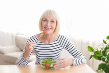 Happy Senior Lady Eating Fresh...