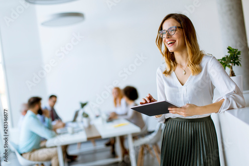 Photo  Elegant businesswoman standing in office with digital tablet