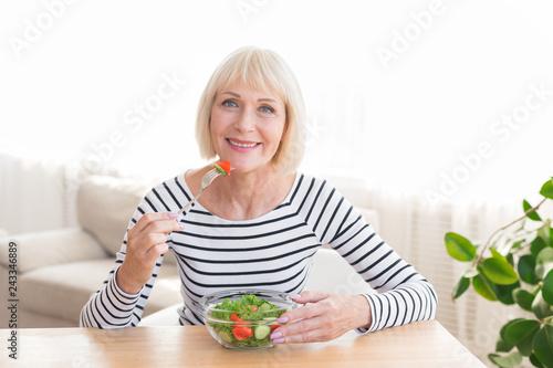 Happy senior lady eating fresh salad at home Fototapeta