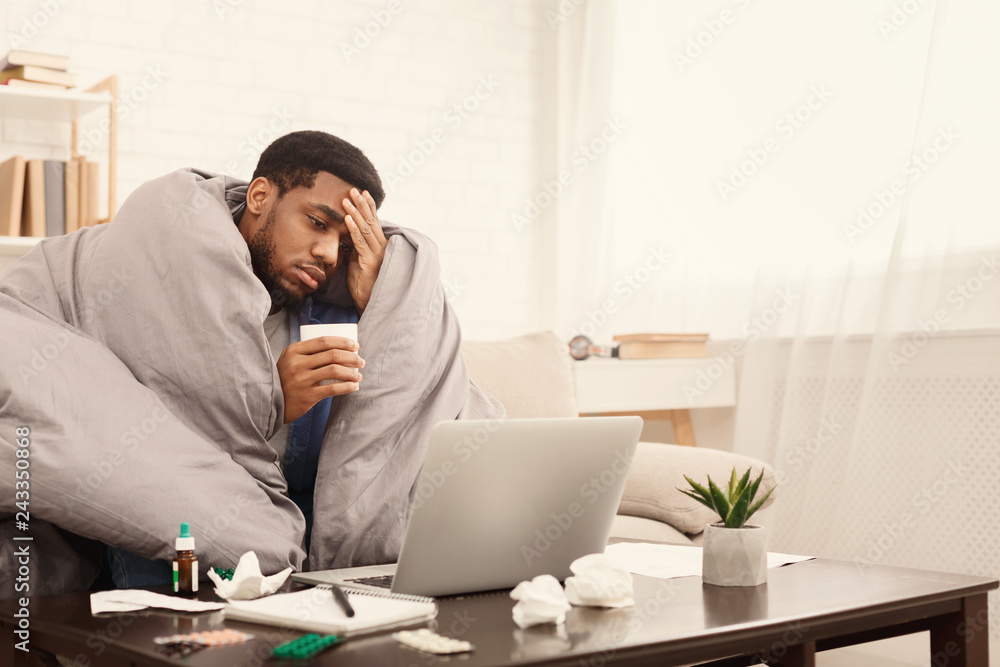 Fototapeta Sick african-american man working on laptop at home