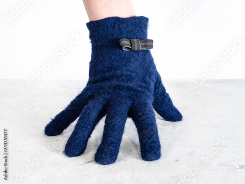 Fotografija  hand in blue glove with bow tie leans on board