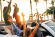 Happy friends having fun in convertible car in vacation - Young people enjoying time traveling and dancing in a cabrio auto during their road trip - Friendship, travel, youth lifestyle concept
