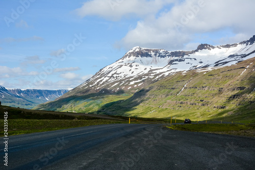 Photo  Mountain view with snow, road and car in summer in Iceland - cloudy day, nice da
