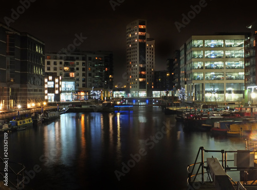 Photo clarence dock in leeds at night with brightly illuminated buildings reflected in