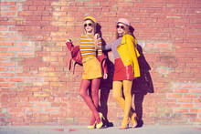 Urban Fashion. Two Girl In Trendy Colorful Outfit Walking, Wearing Stylish Yellow Pink Biker Jacket, Skirt, Heels. Gorgeous Fashionable Woman Friends Relax
