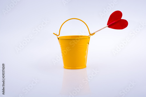Fotografie, Obraz  Yellow color bucket and red heart shape