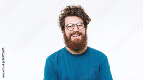 Portrait of smart bearded man in blue sweater looking at camera and smiling
