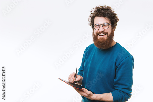 Fotografering  Stylish hispter model in blue pullover looking at camera and hold a tablet