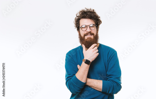 Fotografija  Bearded hispter guy in glasses is posing and looking at camera over white backgr