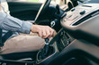 Close up of Caucasian man holding hand on gearshift.