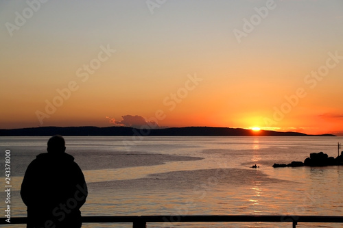 Foto  Silhouete of an unecognizable man watching sunset over the sea.