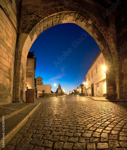Photo  Romantic Prague at dawn, entrance to Charles Bridge through the illuminated arch