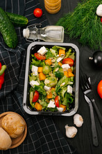 High Angle View Of Vegetable Salad In Plastic Container On Black Wooden Table