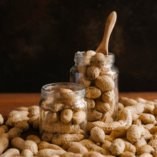 Close Up Of Peanuts In Glass Jars On Wooden Table