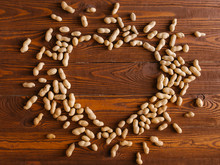 Overhead View Of Peanuts In Heart Shape On Wooden Table