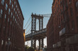 Low angle view of buildings against Manhattan bridge during sunset