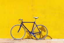 Bicycle Parked On Sidewalk By Yellow Wall During Sunny Day