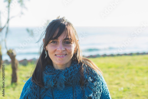Portrait of smiling woman in warm clothing standing on grassy field by sea against clear sky during sunny day
