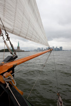 Boat Sailing On River Against Cloudy Sky In City