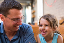 Girl With Missing Teeth Smiling With Father