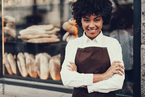 Attractive lady standing near bakery shop and smiling Canvas Print