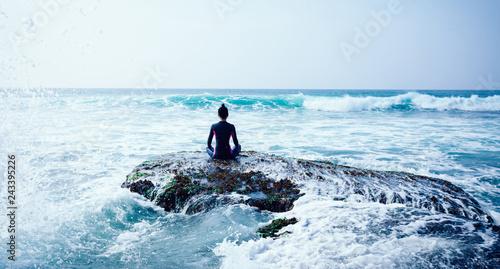 Woman meditation at the seaside croal cliff edge facing the coming strong sea wa Fototapet