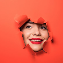 The Face Of A Young Beautiful Girl With A Bright Make-up And With Plump Red Lips Peeks Into A Hole In Orange Paper