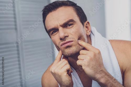 Fotografía  Sad gloomy man touching his cheeks
