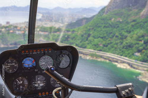 Poster Helicopter View from a helicopter cockpit flying over Rio de Janeiro, Brazil. Cockpit with instruments panel. Captain in the aircraft cockpit. Selective focus, Horizontal