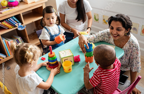 Fotografiet Nursery children playing with teacher in the classroom