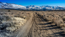 Overview Of HIgh Desert In Nevada Featuring Dirt Road And Snow Capped Mountain