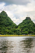Two Limestone Mountains Covered In Jungle Plants With A Buddhist Flag On One Of The Them On The Side Of The River At The Perfume Pagoda In Vietnam