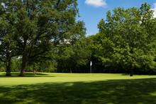 Sun Lit Putting Green And White Flag Through The Tree Shadows.