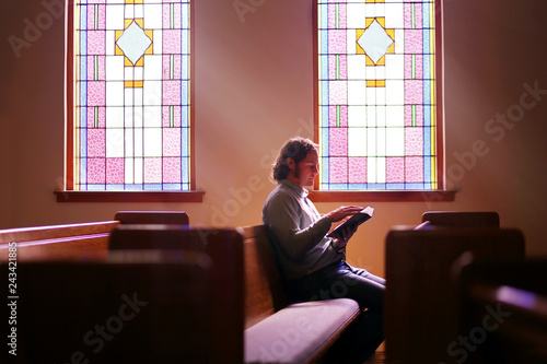 Cuadros en Lienzo Christian Man Sitting Alone in Dark Empty Church Pew by Bright Stained Glass Win