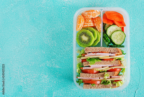 Photo sur Toile Assortiment School lunch box with sandwich, vegetables, water, and fruits on table. Healthy eating habits concept. Flat lay. Top view