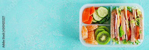 School lunch box with sandwich, vegetables, water, and fruits on table. Healthy eating habits concept. Flat lay. Banner. Top view