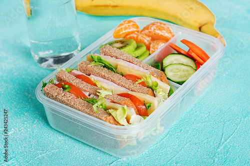 School lunch box with sandwich, vegetables, water, and fruits on table. Healthy eating habits concept.
